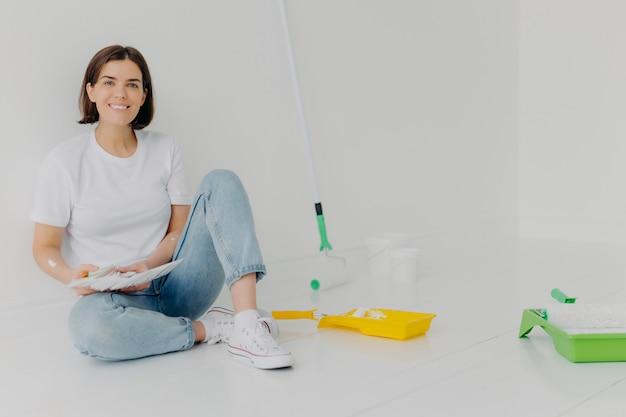 De glimlachende vrouwenontwerper kiest beste kleur voor flat
