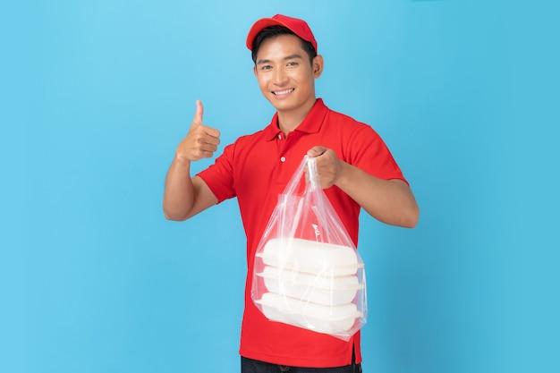 De glimlachende werknemer van de leveringsmens in eenvormige status van het rode glb lege overhemd met het geven van voedselorde die op blauw wordt geïsoleerd