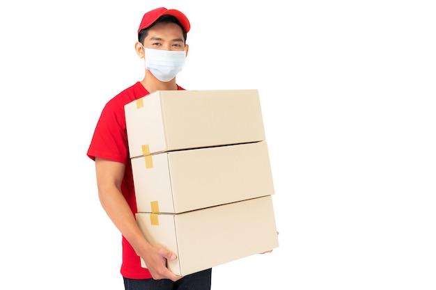 De glimlachende werknemer van de leveringsmens in rode glb lege t-shirt eenvormige status met pakketbrievenbus die op wit wordt geïsoleerd
