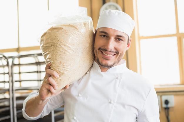 De glimlachende zak van de bakkersholding rijzend deeg