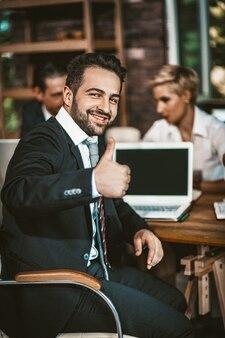 De glimlachende zakenman toont duimen op gebaarzitting op vergadering