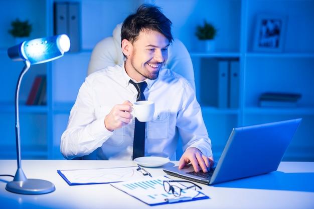 De glimlachende zakenman werkt aan laptop in bureau.