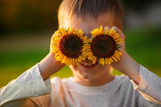 De glimlachende zonnebloemen van de portret glimlachende jongen vóór zijn ogen op de zomerzonsondergang.