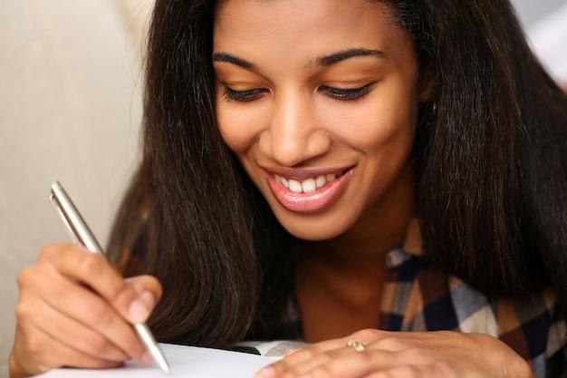 De glimlachende zwarte schrijft verhaal in notitieboekje