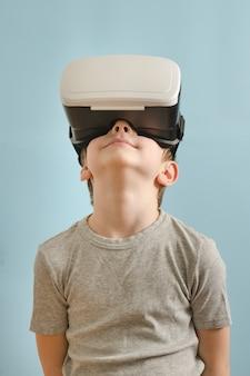De glimlachjongen met glazen virtuele werkelijkheid kijkt omhoog. blauwe achtergrond