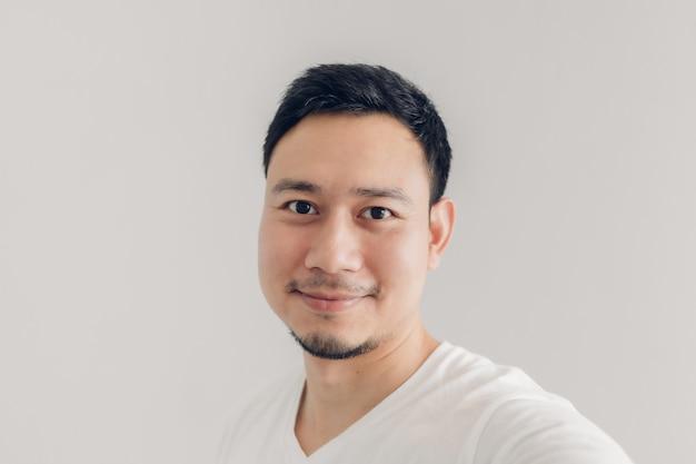 De glimlachmens neemt selfie van zich met wit t-shirt
