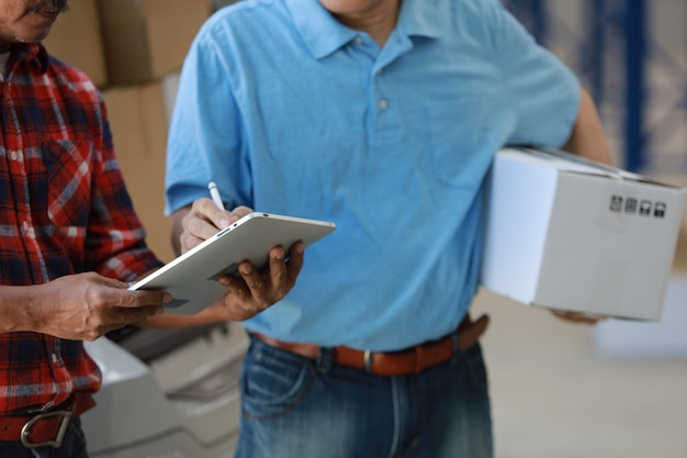 De goede doos van de aziatische mensenlevering aan klant in fabriek en handtekening op tabletglimlach en de goede dienst, logistiek het winkelen online concept
