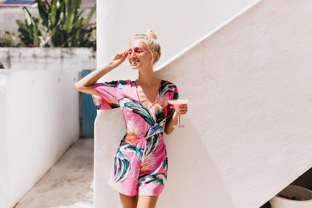 De goedgevormde gebruinde vrouw draagt een elegante zomerjurk die geluk uitdrukt.