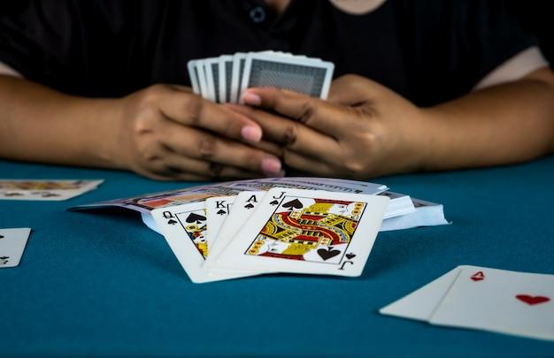 De gokker speelt kaarten in zijn hand.