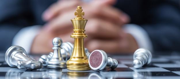 De gold chess king-figuur onderscheidt zich van de menigte van vijand of tegenstander tijdens de schaakbordcompetitie.