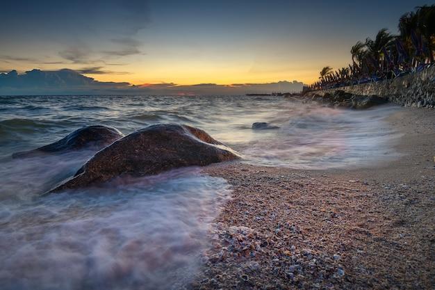De golf op het strand met zonsonderganghemel