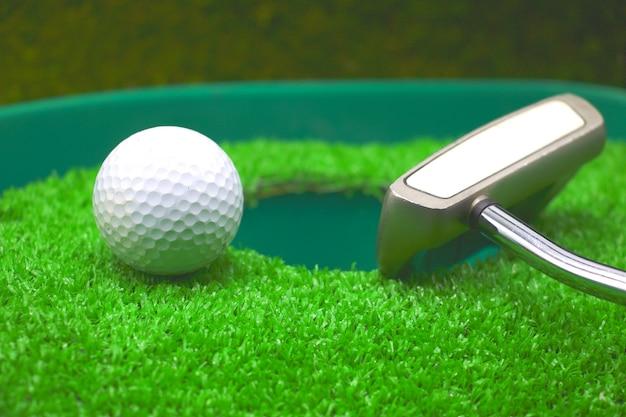 De golfbal met putter is naast het gat op groen gras