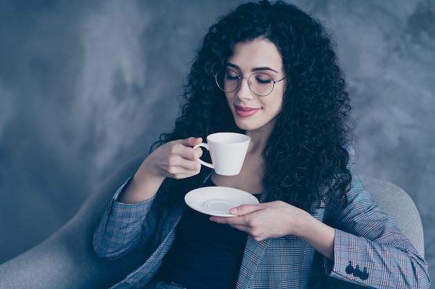 De golvendharige meisjesmanager zit in stoel die hete koffie drinkt die over concrete muur wordt geïsoleerd