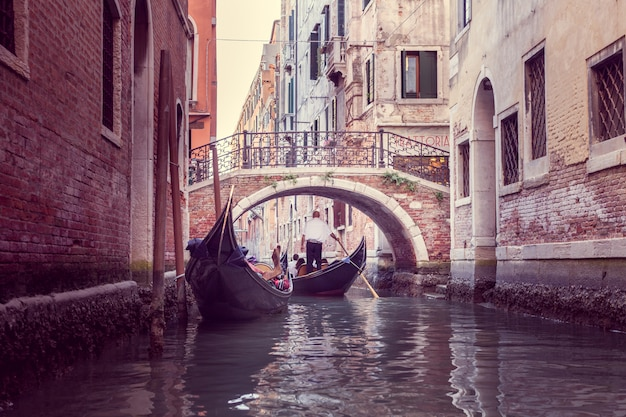 De gondelier drijft op een smal kanaal in venetië