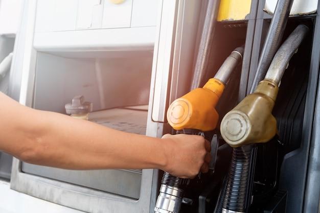 De gouden auto vult de brandstof bij het olie station. hand met brandstofmondstuk in benzinepomp.