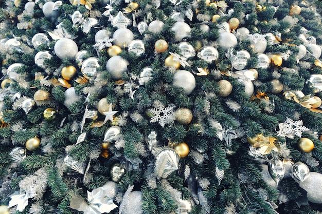 De gouden bal van kleurenkerstmis hangt op groene pijnboomboom met de vage partij van het nacht lichte nieuwe jaar