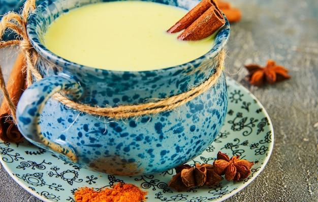 De gouden gezonde drank van de lattekurkuma in een blauwe kop.
