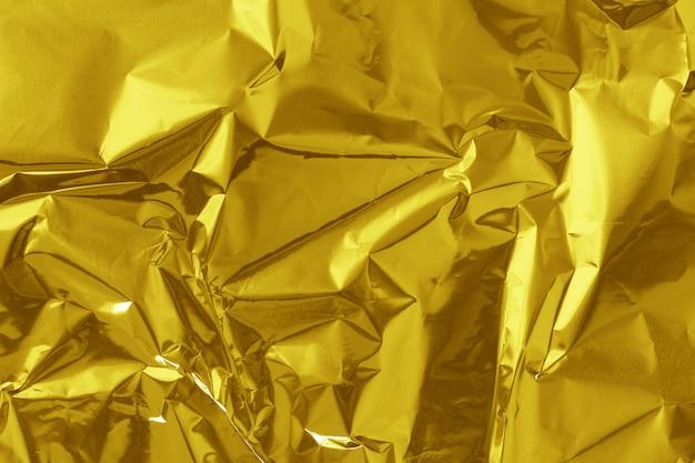 De gouden glanzende textuur van het folieblad, vat geel verpakkend document voor achtergrond samen