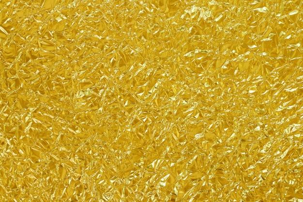 De gouden glanzende textuur van het folieblad, vat gele inpakpapierachtergrond samen