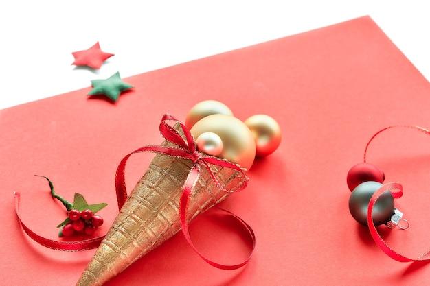 De gouden kegel van het wafelroomijs met gouden snuisterijen van kerstmis, sterren en rode linten op roze document