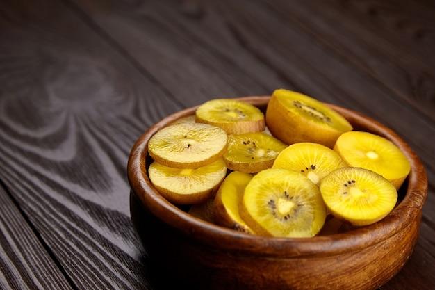 De gouden plakjes van het kiwifruit in houten kom