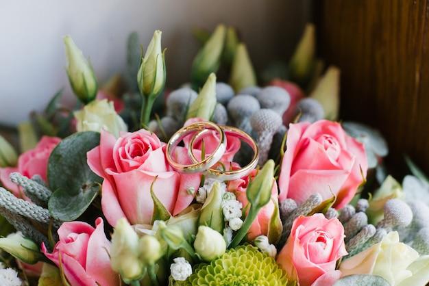 De gouden trouwringen op heldere huwelijksbloemen sluiten omhoog