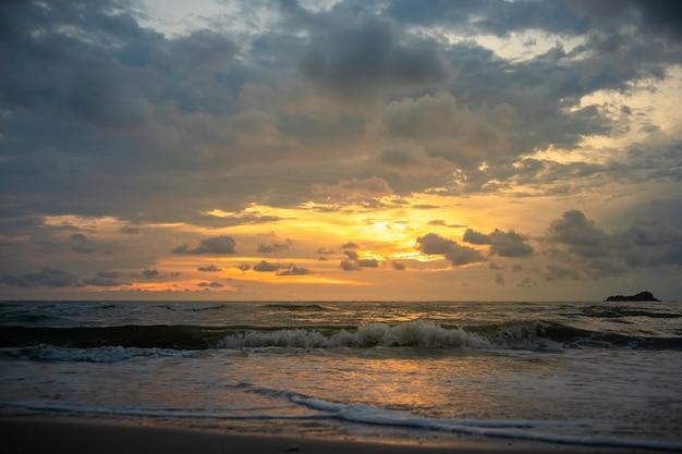 De gouden zonsondergang bewolkte hemel op kalm en maakt het strand schoon.