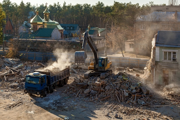 De graafmachine laadt de overblijfselen van het verwoeste gebouw in de auto