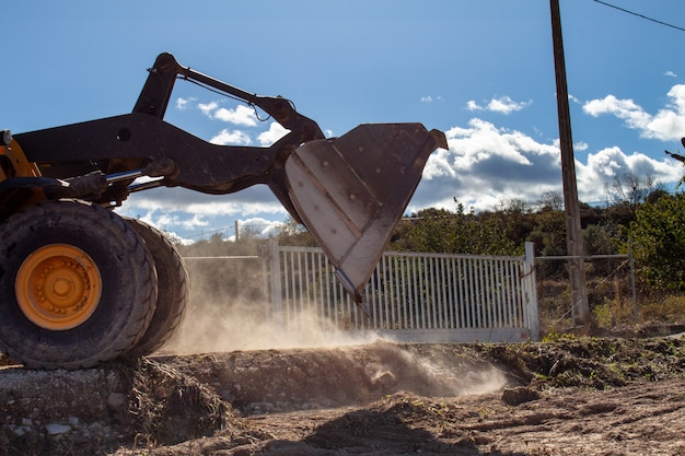 De graafmachine schop verwijdert vuil en boomwegen van een natuurramp