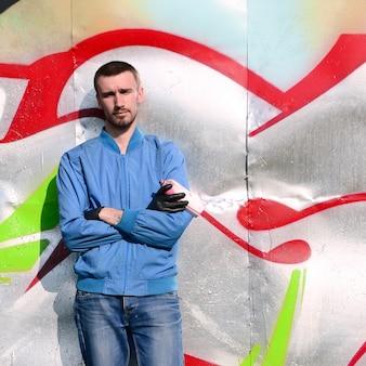 De graffitikunstenaar met spuitbus stelt