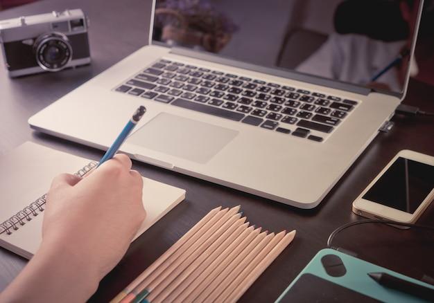 De grafische ontwerperfotograaf werkt met grafische computer