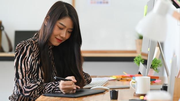 De grafische ontwerpervrouw die aan creatief bureau werken met leidt tot grafisch op computer.