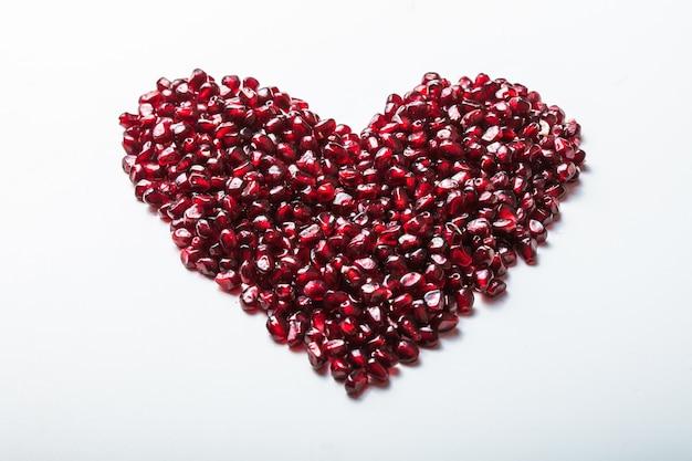 De granaatappelzaden van de hartvorm op wit.