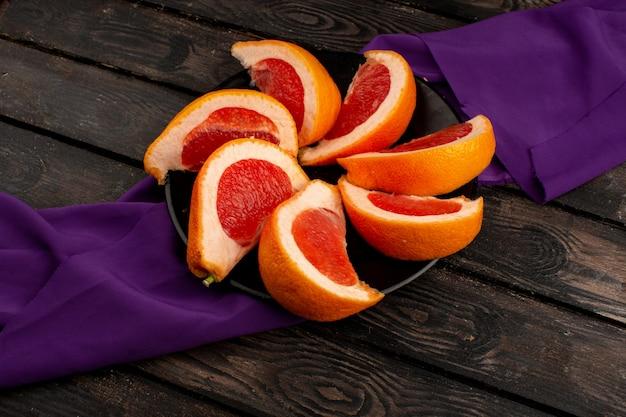 De grapefruit snijdt oranje sappig binnen zwarte plaat op een purpere tissue en een houten bruin houten bureau