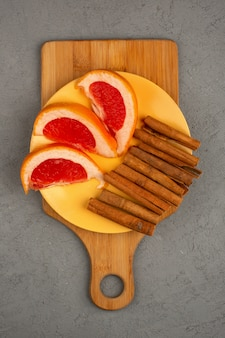 De grapefruit snijdt vers sappig binnen gele plaat samen met kaneel op een grijs bureau