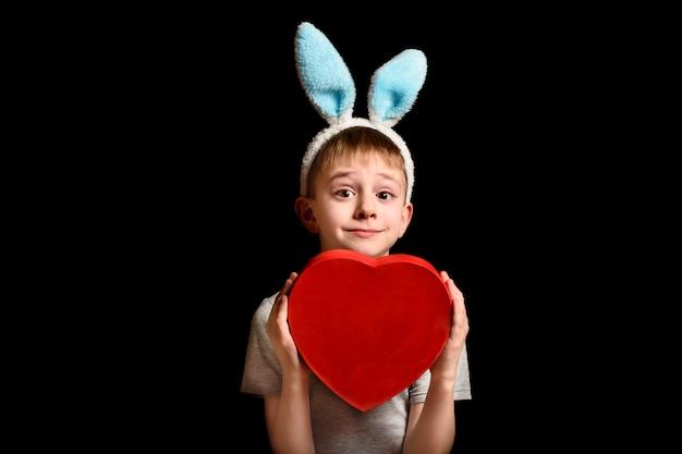 De grappige blonde jongen in hazenoren houdt de rode doos van de hartvorm op zwarte achtergrond. liefde en familie concept. kopieer spase