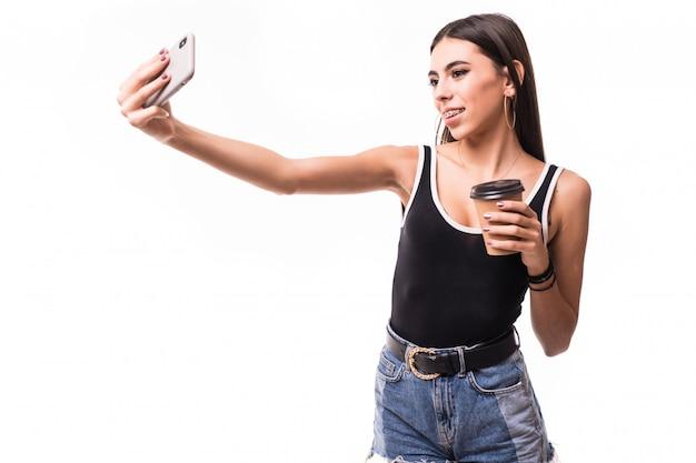 De grappige dame in het kort met koffiekop maakt selfie op haar geïsoleerde telefoon