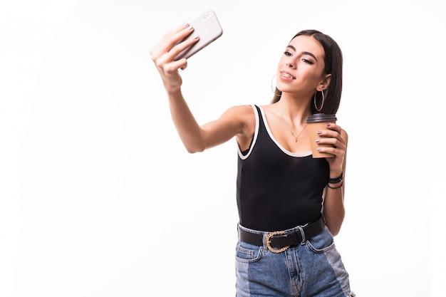 De grappige dame met donkerbruin haar maakt selfie op haar telefoon geïsoleerd