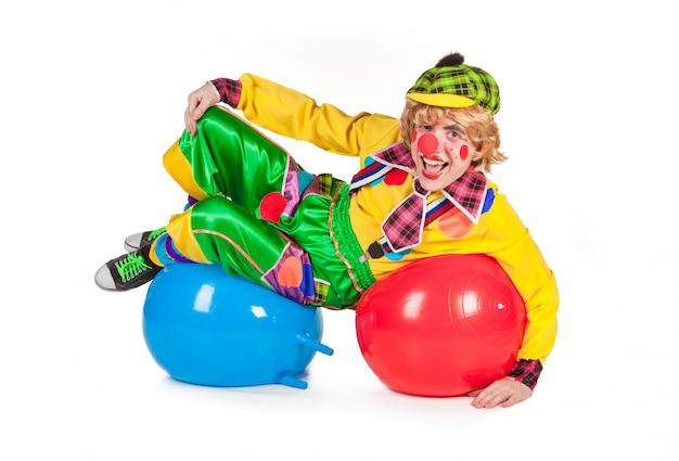 De grappige die clown ligt op ballen op wit worden geïsoleerd