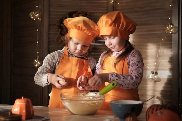 De grappige jongen en het meisje in oranje chef-kokkostuums bereiden pompoentaart voor. kinderen maken zich klaar voor thanksgiving. het concept van een gezinsvakantie