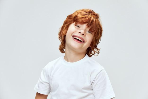 De grappige jongen hield zijn hoofd schuin naar een kant, een brede glimlach bijgesneden