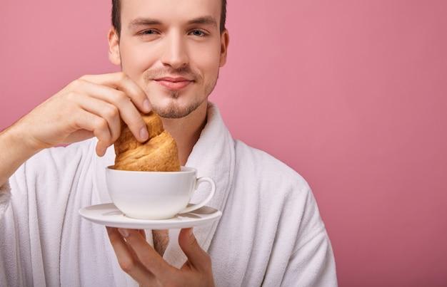De grappige kerel in sneeuwwitte badjas dompelt croissant in thee onder