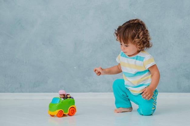 De grappige leuke krullende peuter zit spelend in de auto op een witte vloer op de achtergrond van de grijze muur.