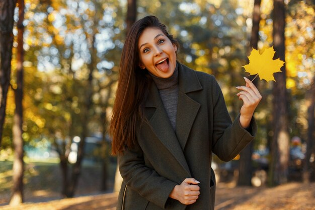 De grappige mooie gelukkige jonge vrouw in modieuze vacht toont tong en houdt gele herfstblad in het park. vrolijke emotie
