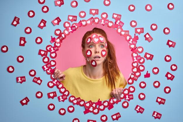De grappige verraste roodharige vrouw bevindt zich in shock door veel tarief voor post te krijgen, houdt van tekensknopen in vorm van hart op gezicht geïsoleerde blauwe muur