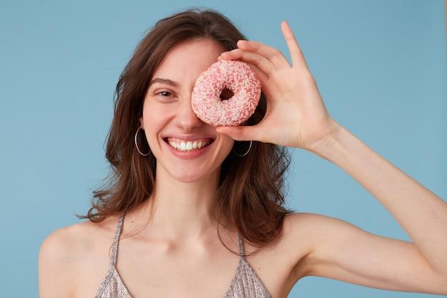 De grappige vrouw behandelt één oog met zoete roze doughnut houdt het in hand, over geïsoleerde blauwe muur