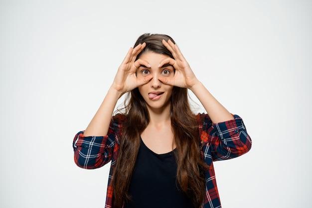 De grappige vrouw maakt glazen met handen en toont tong