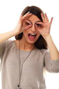 De grappige vrouw maakt glazen met vingers