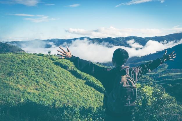 De grappige wandelaar met opgeheven dient de lucht op rotsrand in nationaal park in. levendig en sterk vignetteneffect.