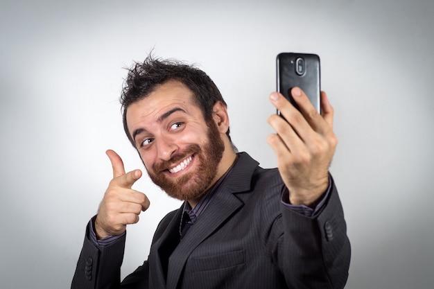 De grappige zakenman gebruikt zijn smartphone om een selfie te nemen